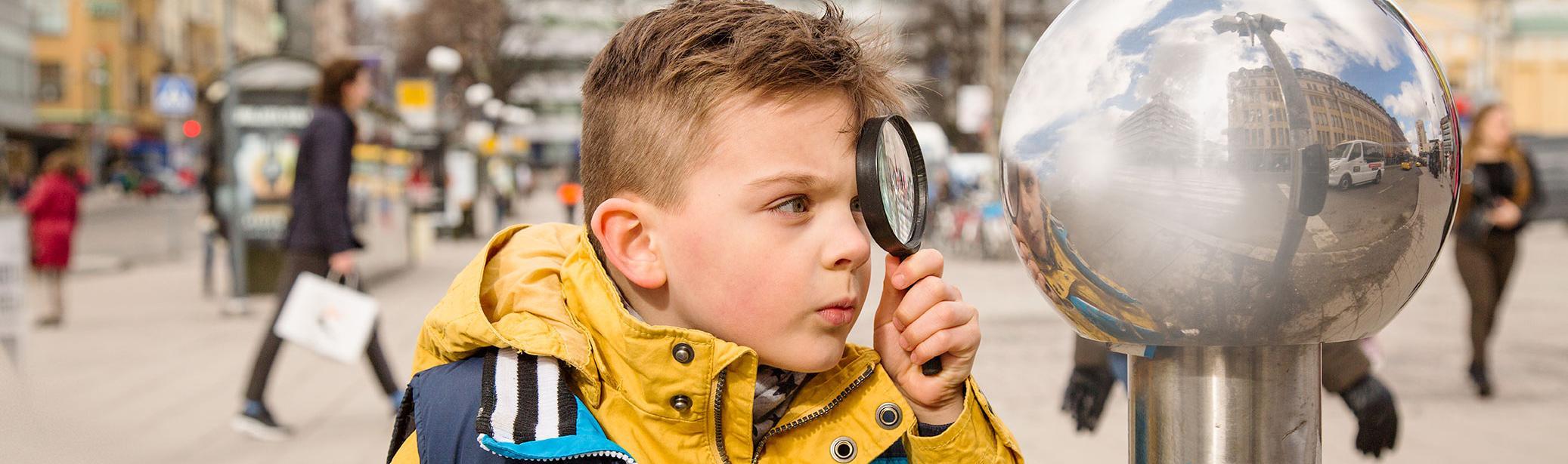 Poika katsoo kaukolämpökaivon tuuletusputkea suurennuslasin läpi.