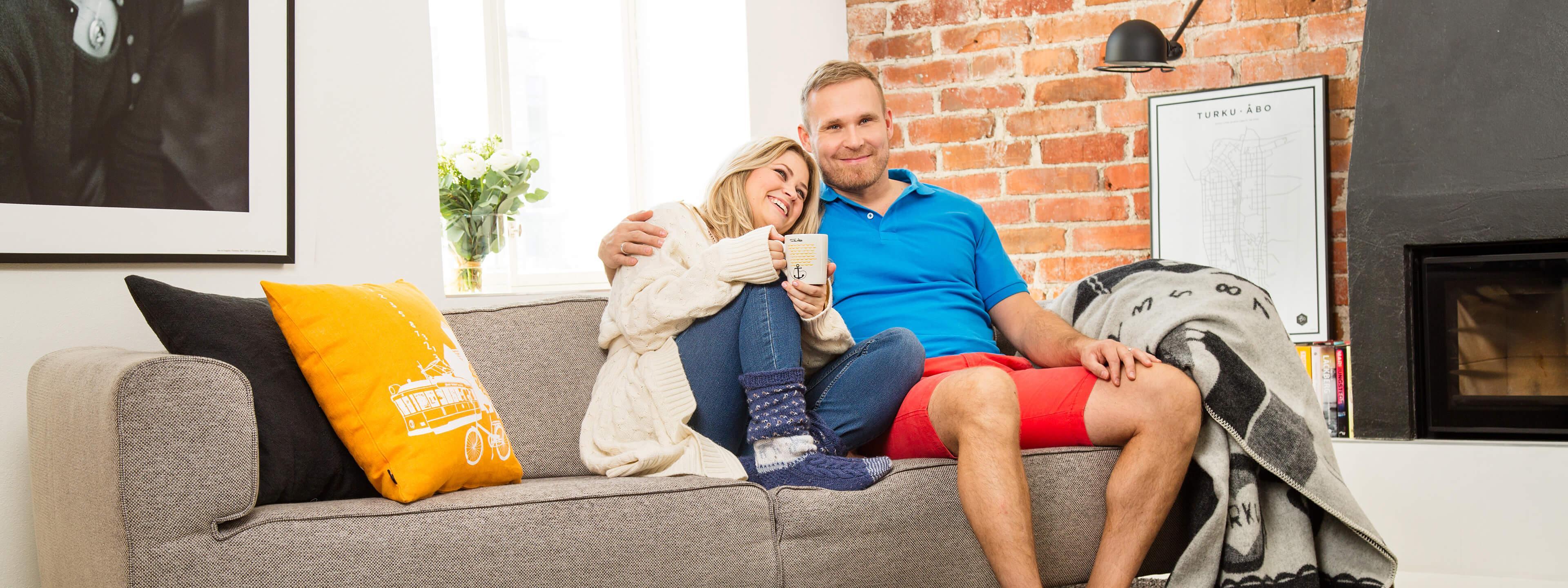 Perhe Valosen pariskunta istuu yhdessä sohvalla.