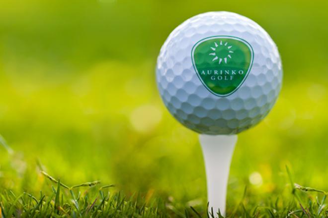 Aurinko Golf, lähikuva golfpallosta tiin päällä.