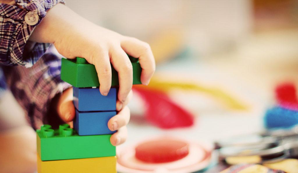 Lähikuva, lapsi kokoaa legoja.