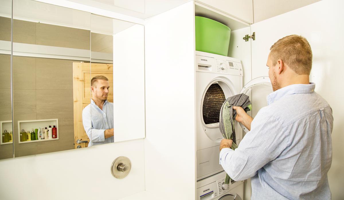 Perhe Valosen isä laittaa pyykkejä koneeseen.