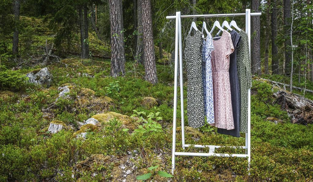 Metsän keskellä vaaterekki, jossa vaatteita roikkumassa.