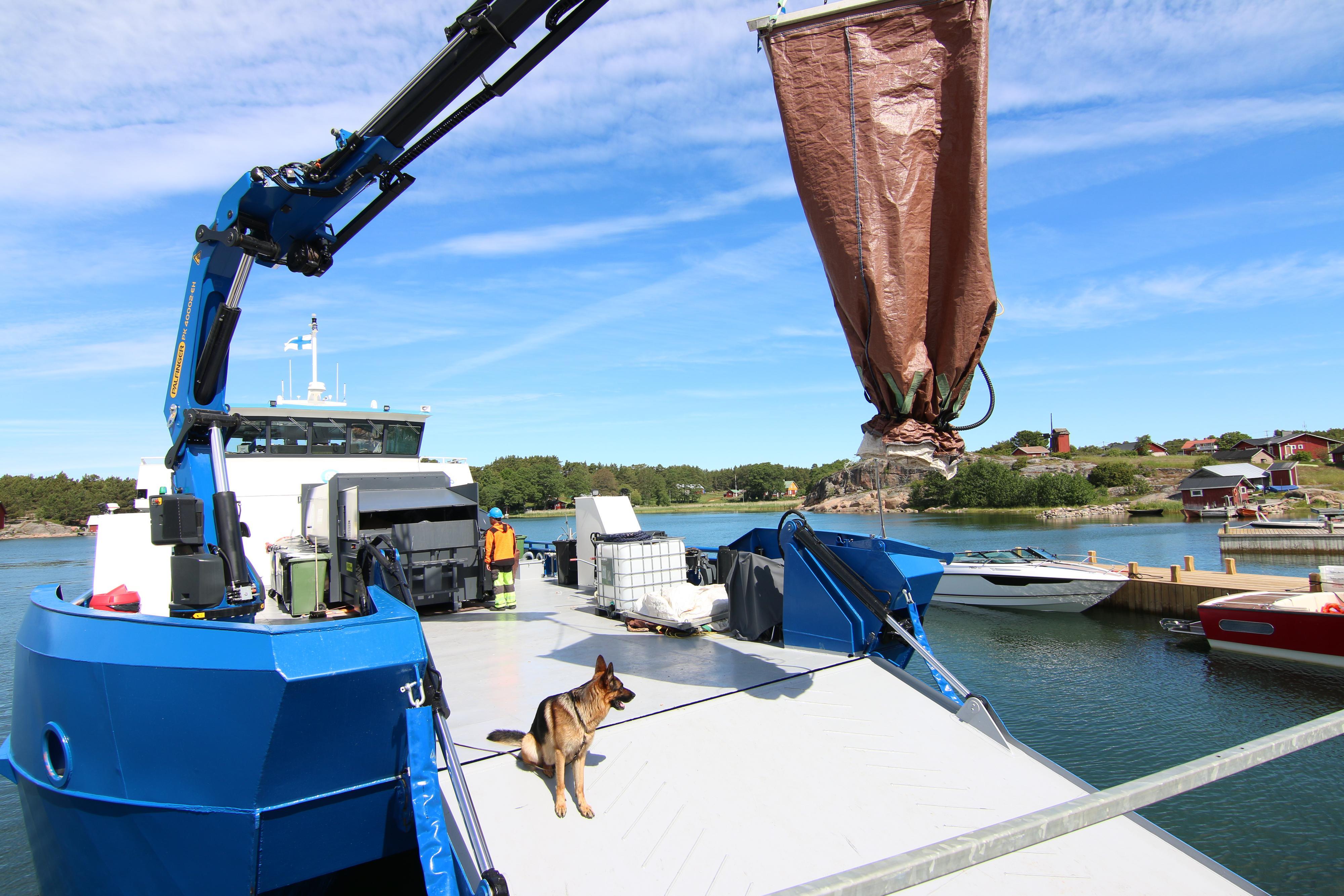 Nosturilla varustetussa veneessä istuu koira.