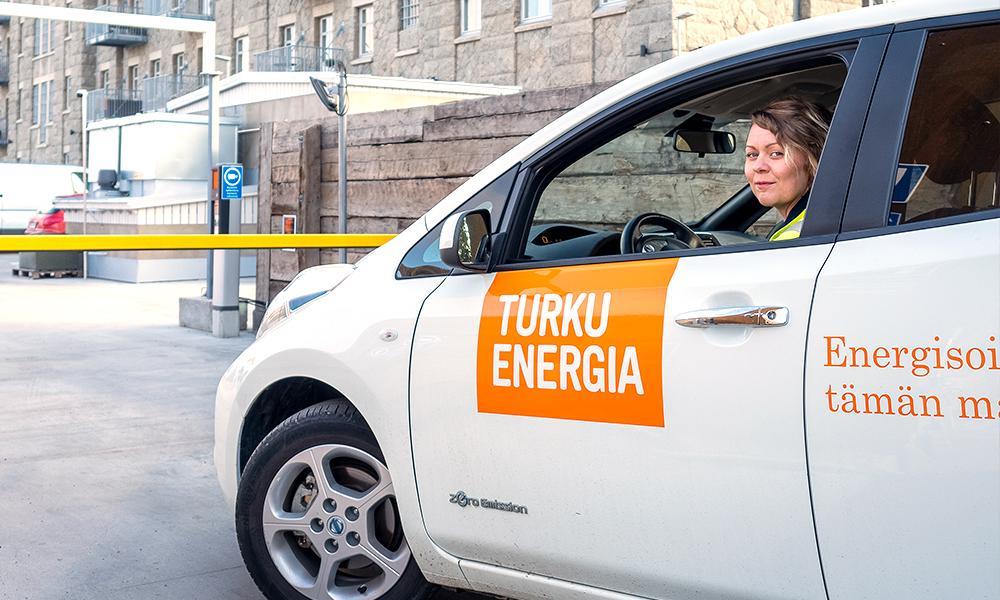 Turku Energian sähköauto, jonka sisällä istuu työntekijä.