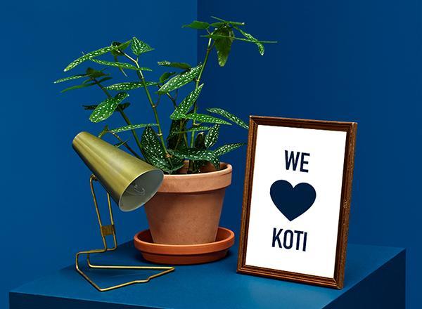 """Pöydällä valaisin, huonekasvi ja taulu, jossa lukee """"WE sydän KOTI""""."""