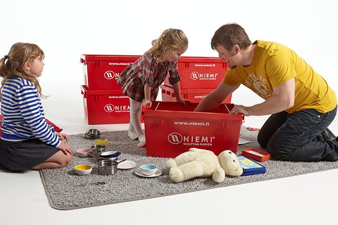 Isä ja lapset muuttolaatikoiden ympärillä.