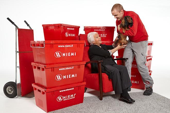 Mies ja vanhus muuttolaatikoiden ympäröimänä.