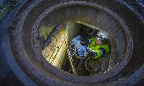 Teemu Mikkola kaivossa asentamassa kaukolämpökaivon valvonta-anturia.