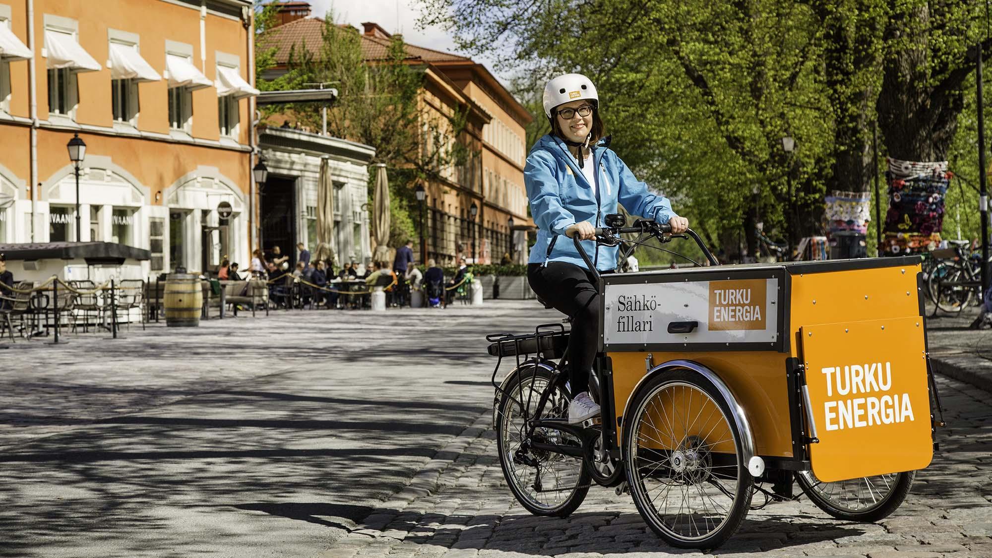 Turku Energian työntekijä pyöräilemässä sähköpyörällä.