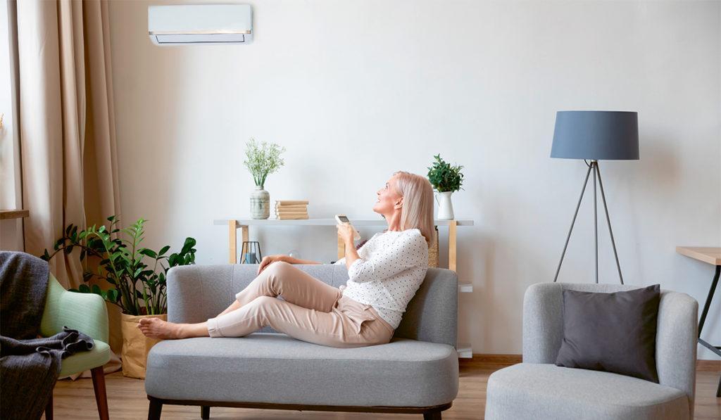Nainen istuu sohvalla ja osoittaa kaukosäätimellä ilmalämpöpumppua.