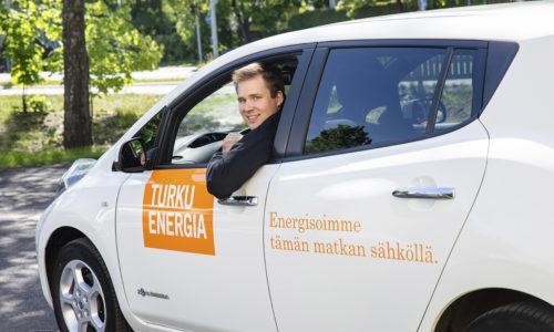 Mies istuu sähköauton kuskin paikalla ja katsoo avonaisesta ikkunasta ulos.