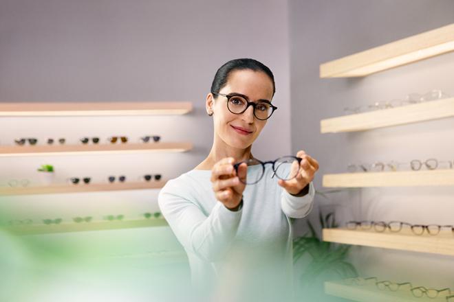 Nainen pitelee silmälaseja optikkoliikkeessä.