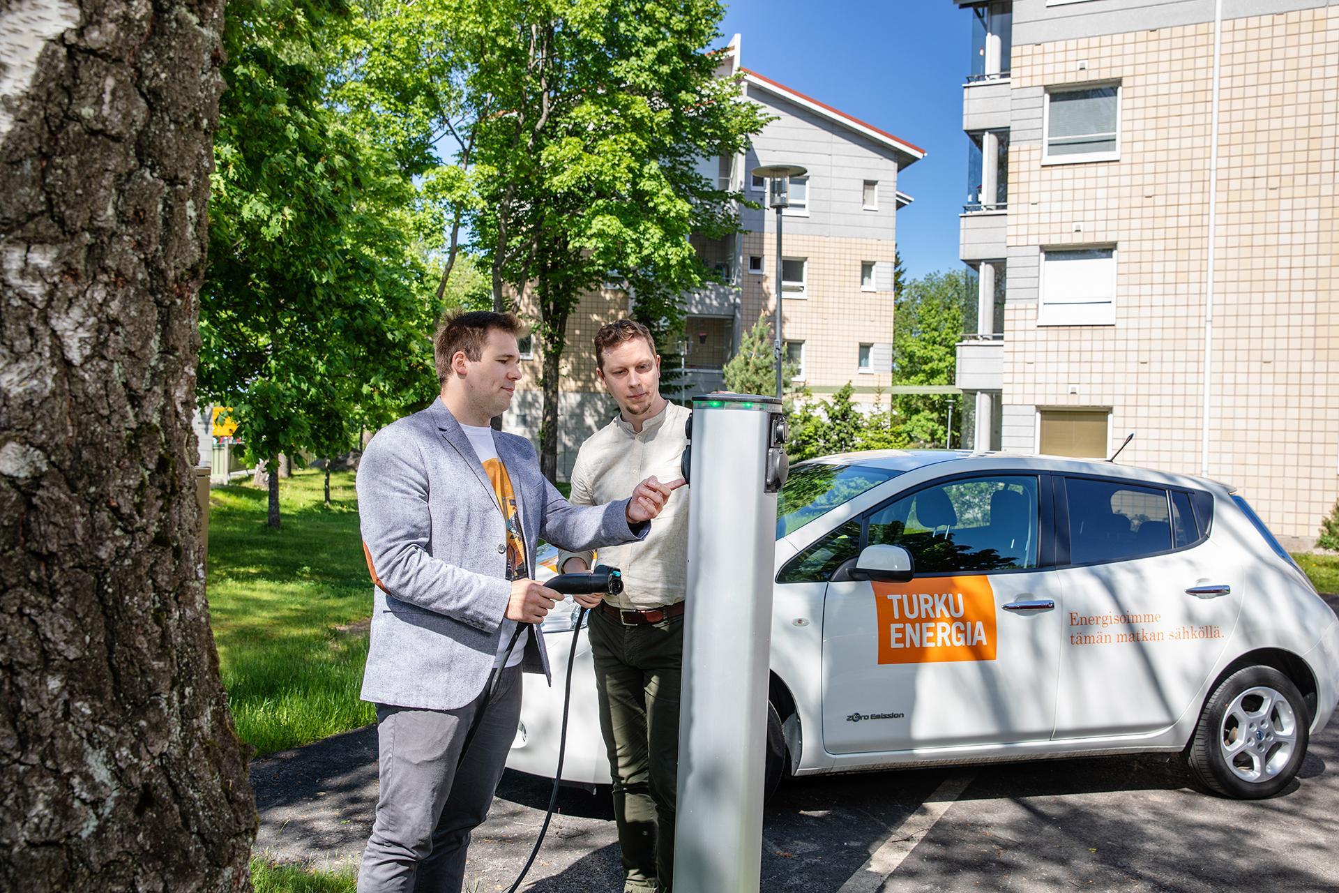 Kaksi miestä tutustumassa sähköauton latauslaitteeseen kerrostalon parkkipaikalla.