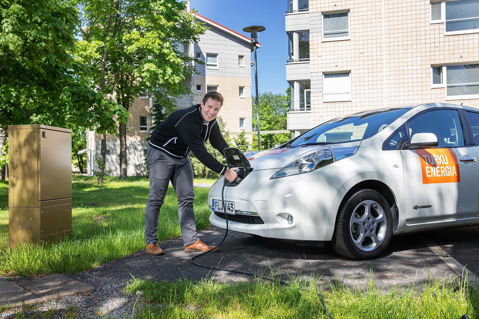 Mies lataa sähköautoa.