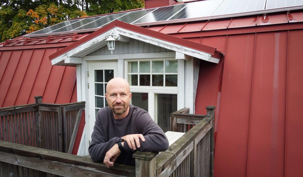 Omakotitalon katolla on aurinkopaneelit. Asukas Mikko Hallamaa hymyilee talon parvekkeella.