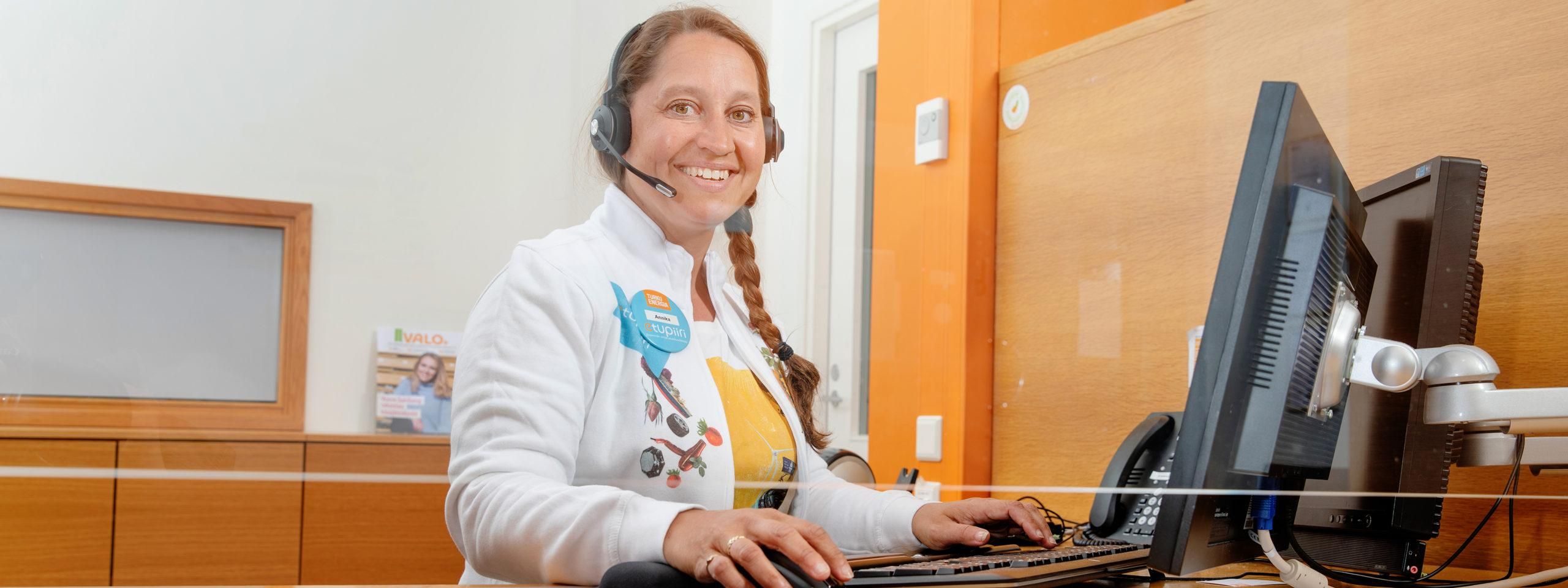 Turku Energian asiakaspalvelija hymyilee tietokoneen äärellä.