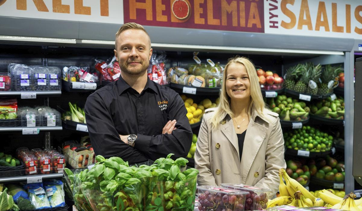 Jasper Wilenius ja Laura Vihavainen hymyilevät vierekkäin K-marketin vihannesosastolla.