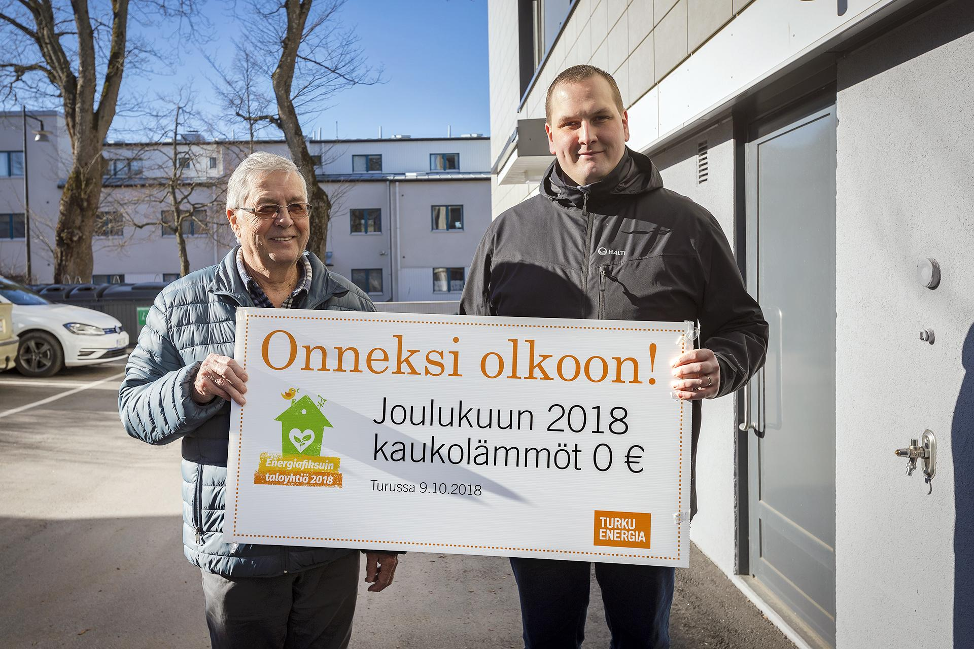 """Kaksi miestä pitelee suurta sekkiä, jossa lukee """"Onneksi olkoon! Joulukuun 2018 kaukolämmöt 0 €""""."""