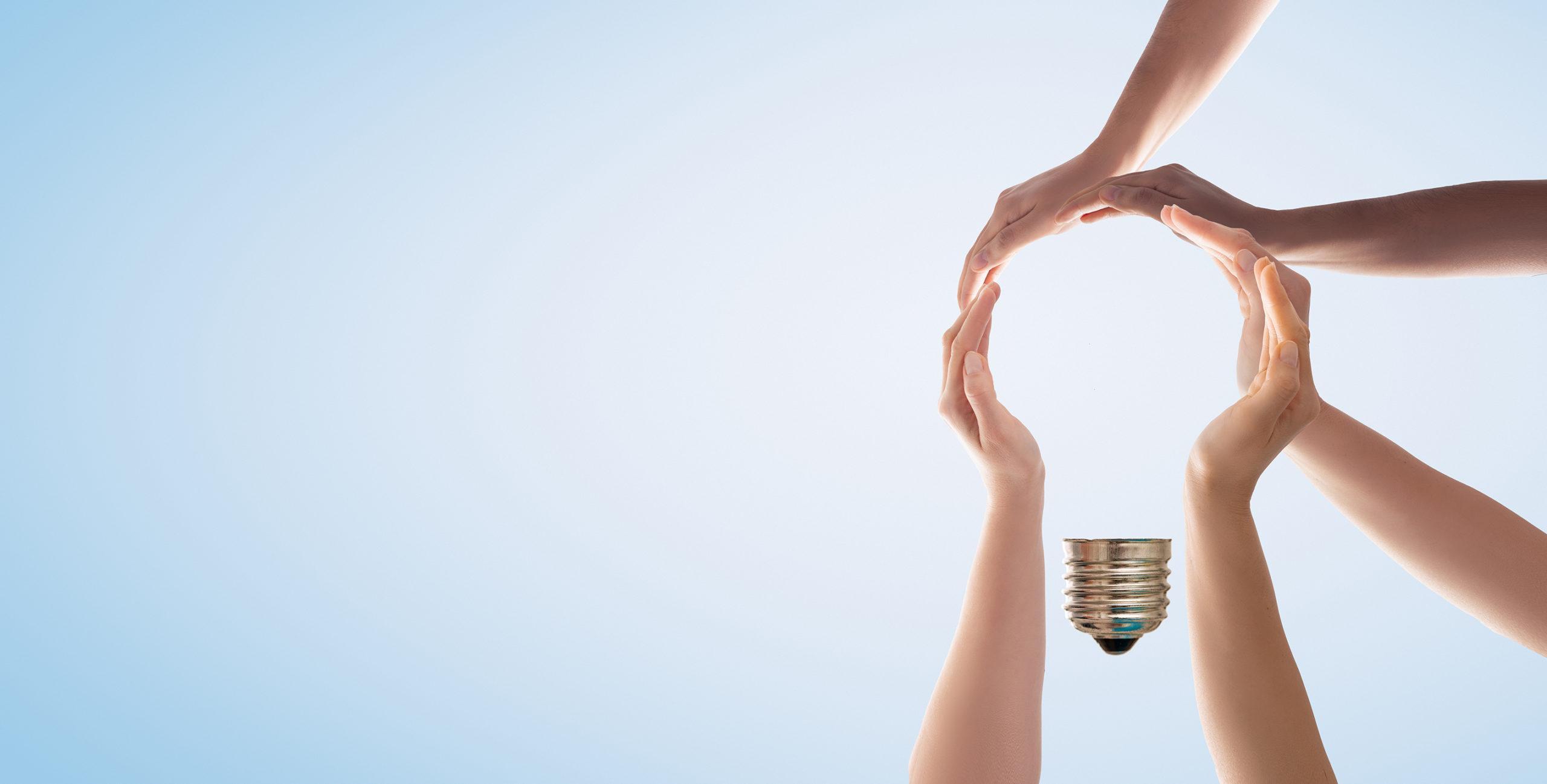 Viisi kättä muodostaa lampun ääriviivat.