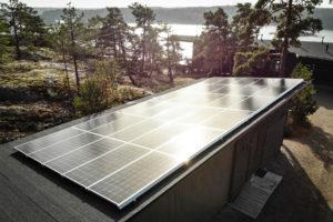Aurinkopaneeleja talon katolla aurinkoisessa metsämaisemassa.