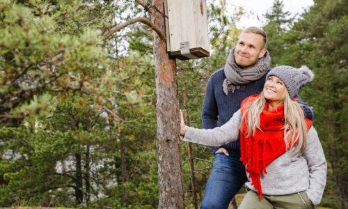 Nainen ja mies seisovat vierekkäin metsässä katsellen hymyillen männyssä olevaa linnunpönttöä.
