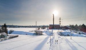Luminen maisema Turun Koroisilla. Aurinko paistaa Koroisten sähköaseman piipun takaa.