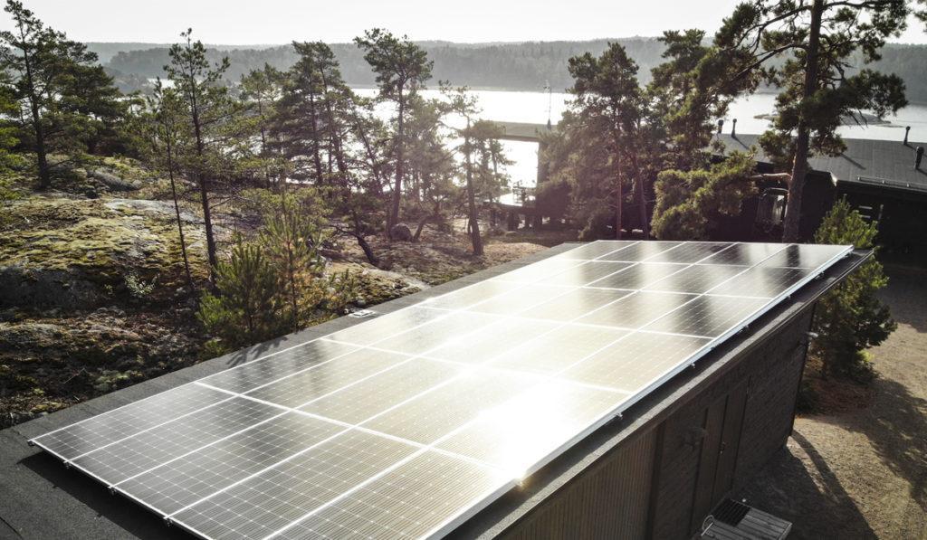 Aurinkopaneelit talon katolla aurinkoisessa metsämaisemassa.