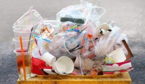 Erilaisia muoviroskia lähikuvassa roska-astian päällä.