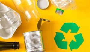 Tyhjiä lasi- ja muovipulloja sekä kierrätystä kuvaava symboli.