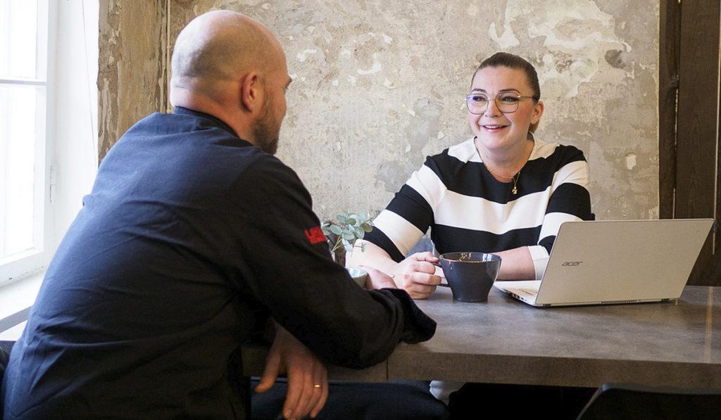 Niklas ja Eva Halenius istuvat pöydän ääressä katsellen hymyillen toisiaan.