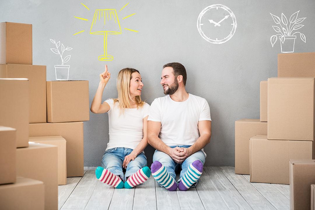 Nainen ja mies istuvat huoneen lattialla muuttolaatikkopinojen vieressä.