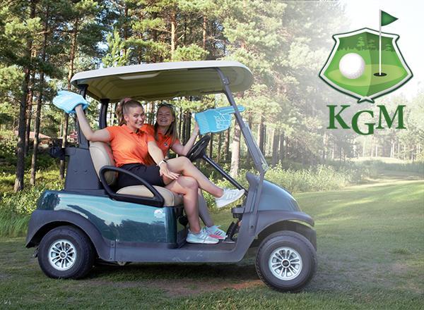 Kaksi nuorta naista hymyilee golfkärryn kyydissä.
