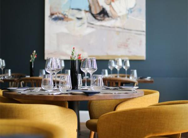 Ravintolapöytä ja taulu seinällä.
