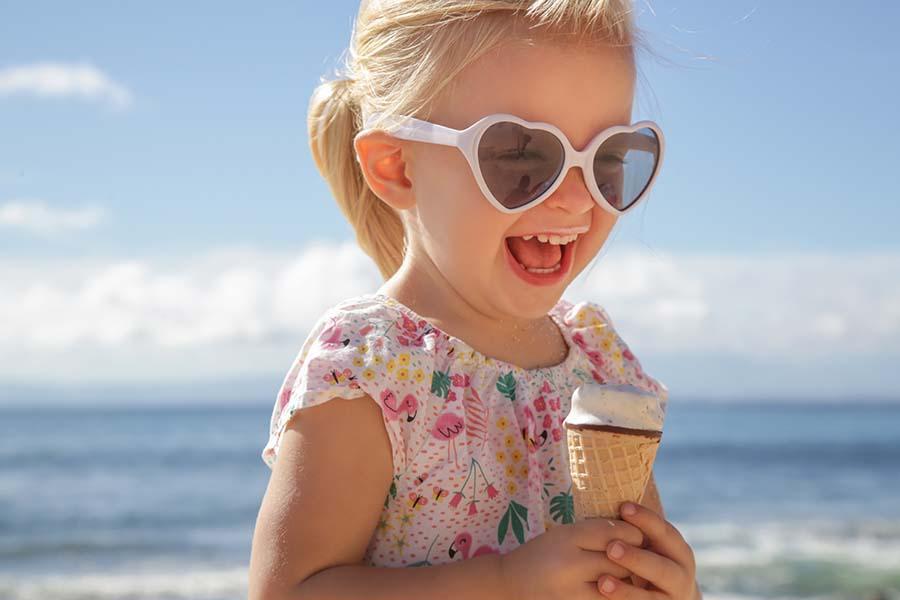 Tyttö syö rannalla jäätelöä, meri ja sininen taivas takana.