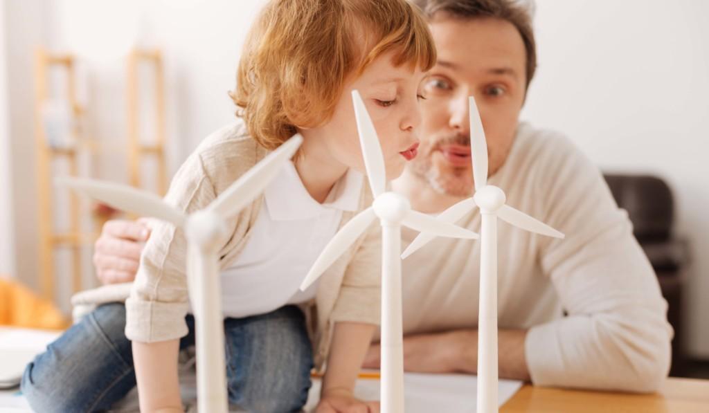 Isä ja poika puhaltavat tuulimyllyjen pienoismalleja.