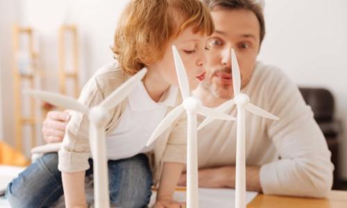 Isä ja poika hassuttelevat tuulimyllyjen kanssa.
