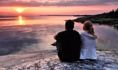 Pari istumassa Itämeren äärellä auringonlaskussa.