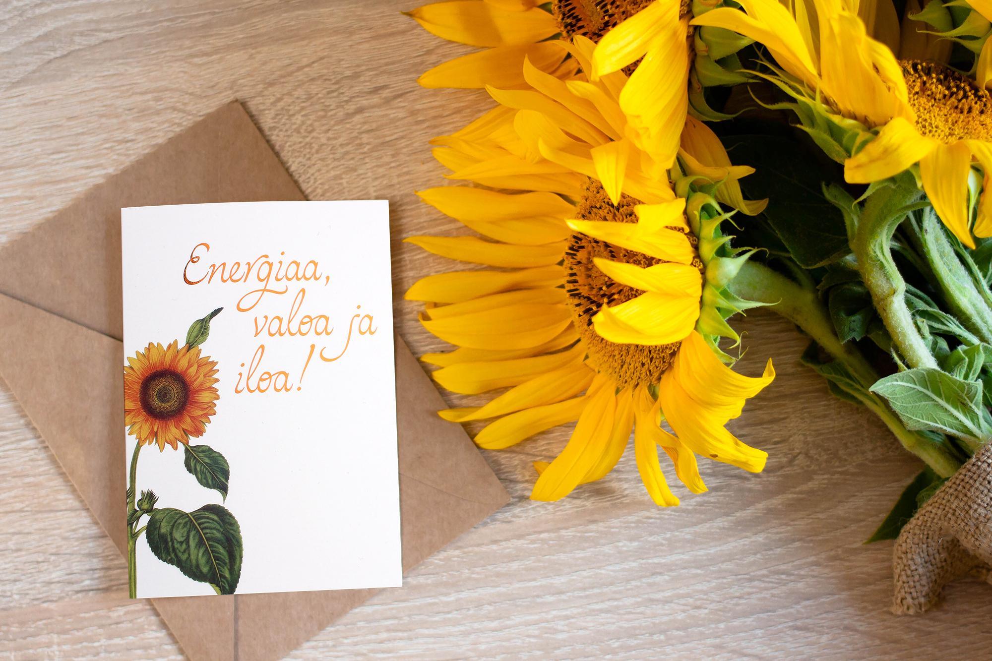 Energialahjakortti pöydällä auringonkukkakimpun vieressä.